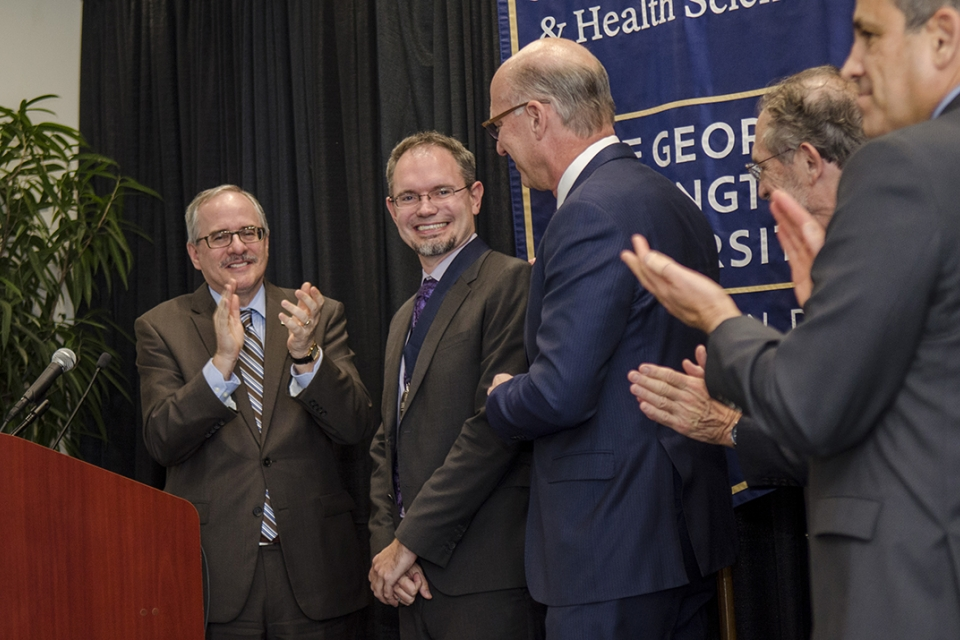 GW President Thomas LeBlanc (l), Brandon Kohrt (second from left) and Dean Akman at the installation of Dr. Kohrt as the Charles and Sonia Akman Professor in Global Pyschiatry