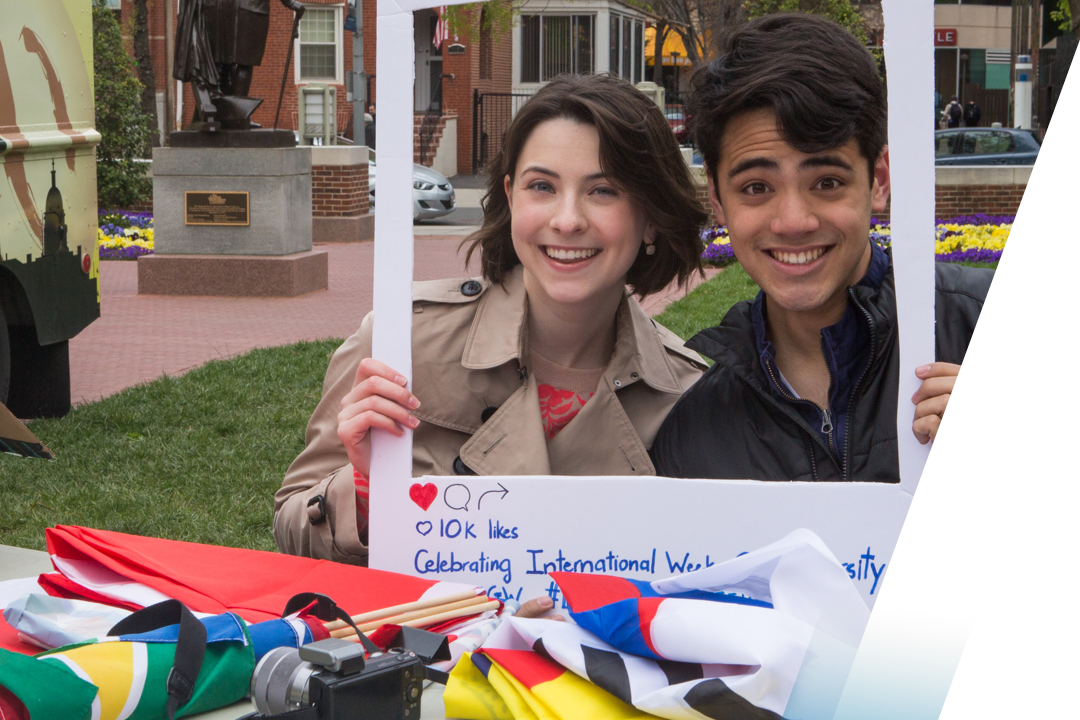 Male and female students posed with props on campus