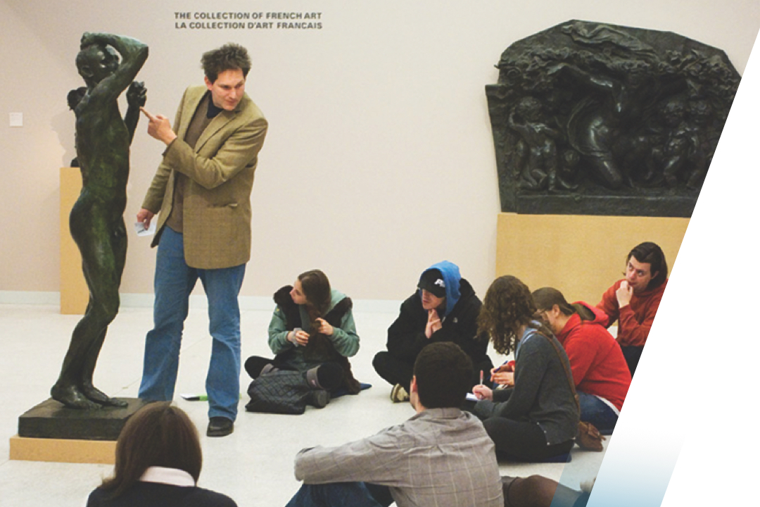 Professor lecturing students with a statute in a museum