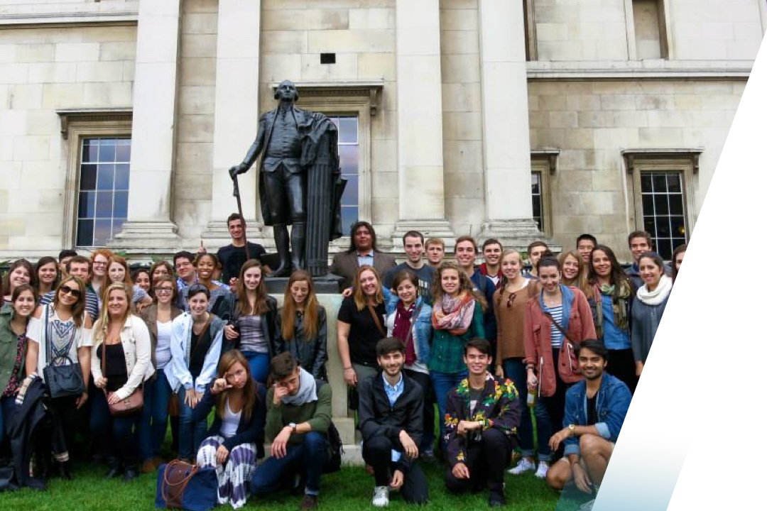 Large group of students posed with a statue